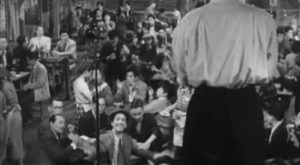 A man onstage in a white shirt with his back to us sings in a crowded Japanese beer hall