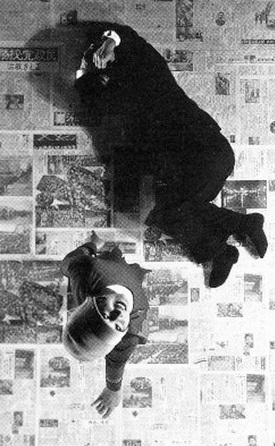 Photo from above of a man in a suit lying about a floor covered in newsprint with a woman standing over him