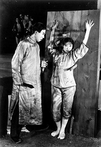 A photo of a woman bound to a wall and being threateningly addressed by a taller man, both in traditional Japanese clothing