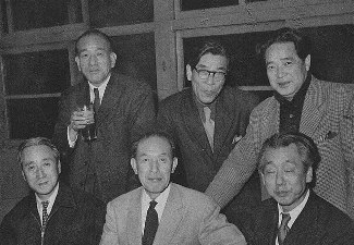 Six middle-age Japanese men in suits, three of them seated, the other three standing behind them.