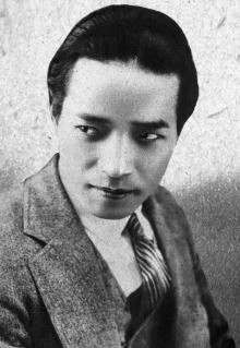 A publicity photo of a young Japanese man in a suit