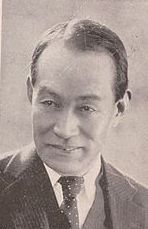 Image of a smiling middle-aged Japanese man in a suit, looking at something off-camera