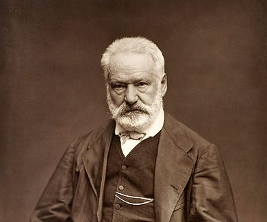 A portrait of an old bearded man, Victor Hugo, seated, and looking unsmiling at the camera