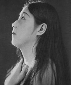 A young Japanese woman looking up, her hands just below her neck
